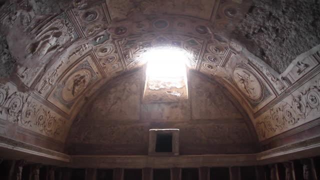 vídeos de stock, filmes e b-roll de tracking the ceiling of the forum baths towards a shaft of light, pompeii, napoli - ruína antiga