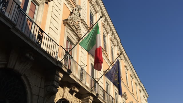 tracking the national italian flag and european flag hanging from a building in rome - italienische flagge stock-videos und b-roll-filmmaterial