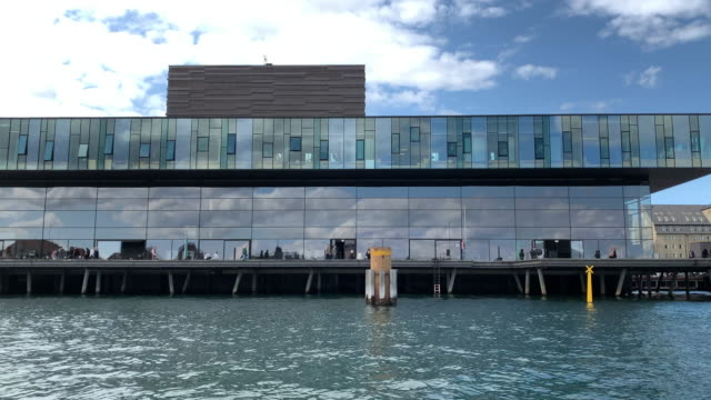 tracking the royal danish playhouse, seen across the water, copenhagen - regione dell'oresund video stock e b–roll
