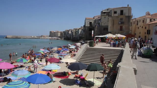 tracking the stunning, picturesque beach and town of cefalu, sicily - italien stock-videos und b-roll-filmmaterial