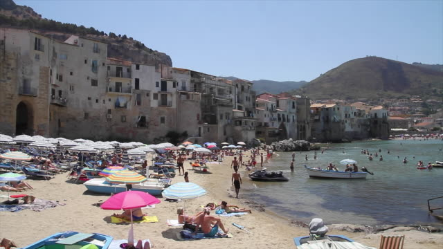 tracking the stunning, picturesque beach and town of cefalu, sicily - ligga ner bildbanksvideor och videomaterial från bakom kulisserna