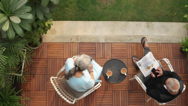 tracking top shot, an elder couple busy on their mobile devices at early morning coffee time - patio stock-videos und b-roll-filmmaterial
