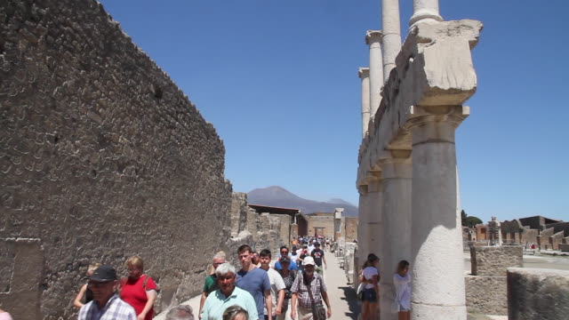 Tracking tourists admiring the ancient colonnades of the ruined Forum, Pompeii, Napoli