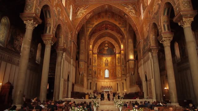 tracking towards a bridal party in the stunningly ornate, gilded cathedral of monreale in palermo, sicily, italy - catholicism stock videos & royalty-free footage