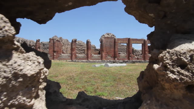 tracking towards a hole in a wall through which can be seen the ruined colonnades of pompeii, napoli - foro video stock e b–roll