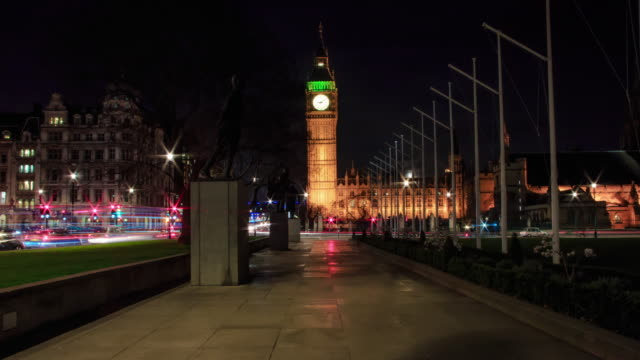 Tracking towards the Elizabeth clock face tower AKA Big Ben at night with streaking car lights, London Buses and clouds flashing across the sky.