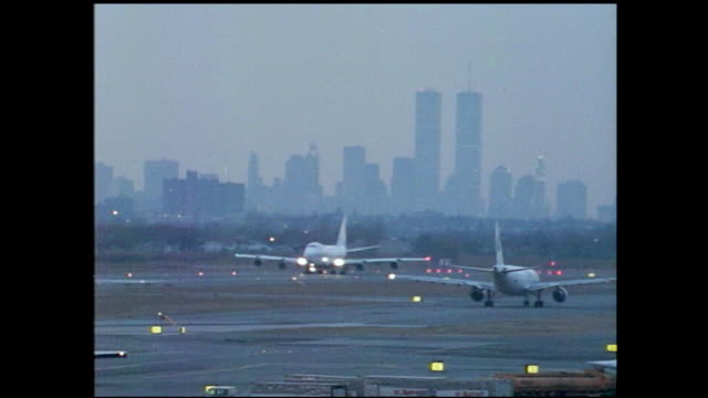 """tracking view of airplane flying in the sky with letters """"american west ...""""; planes taxiing on the runway at airport at dusk, city silhouette in the... - new york city stock videos & royalty-free footage"""