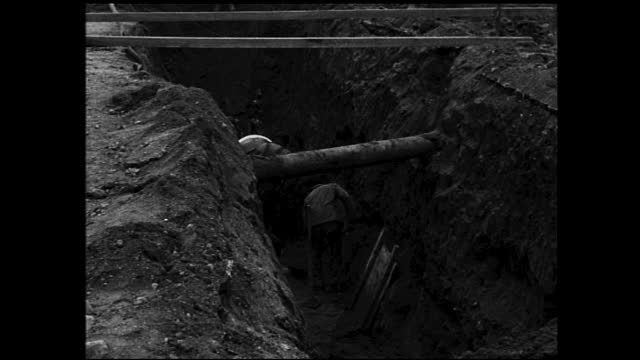 vidéos et rushes de tracking view of crane lifting large concrete pipe into ditch, workers digging inside the ditch and some workers standing by; neighborhood in the... - 1940 1949
