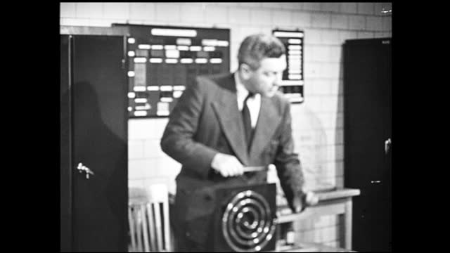 vídeos de stock e filmes b-roll de tracking view of man in suit carrying scientific model and setting it on the table, presenting it to two other men in suits sitting around the table;... - 1940 1949