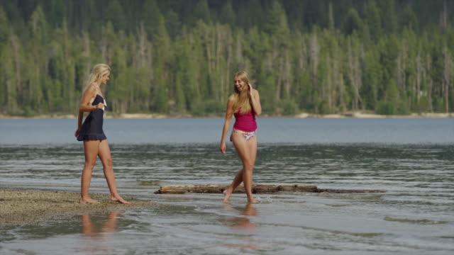 tracking wide shot of young women splashing in lake / redfish lake, idaho, united states - full length点の映像素材/bロール