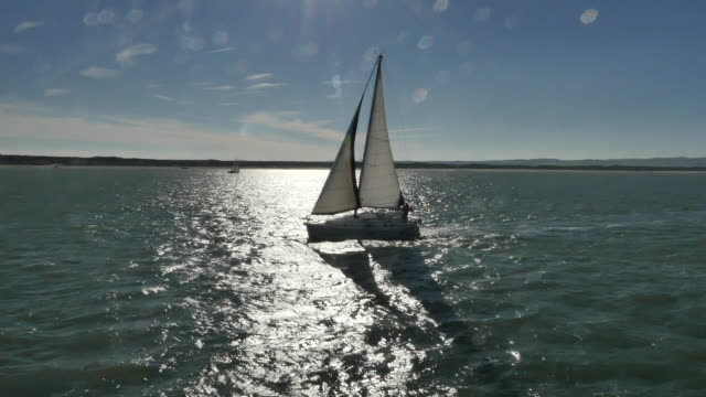 tracking wide shot with lens flare of a moving sailboat bathed in a ray of sunlight, uk. - sailing stock videos & royalty-free footage