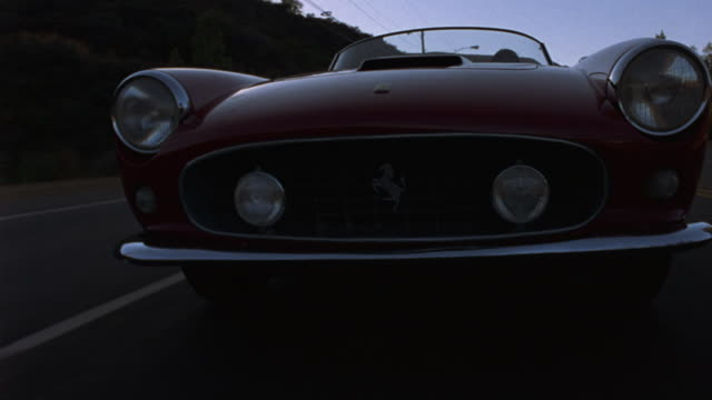 tracking-in of a vintage ferrari traveling down a los angeles highway. - expense stock videos and b-roll footage