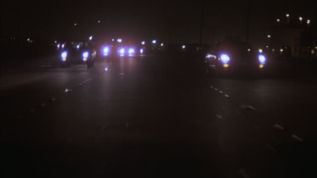 Tracking-out shot of vehicles driving on a freeway at night.