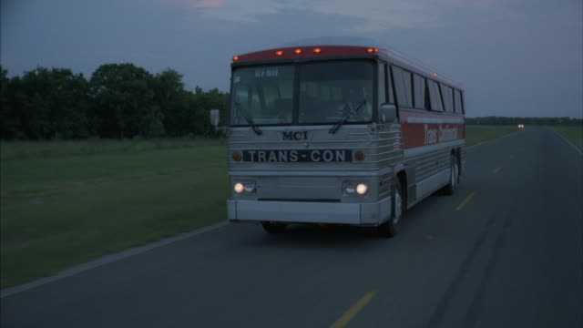 vídeos de stock, filmes e b-roll de tracking-shot of a silver tour bus driving down a rural highway. - bus