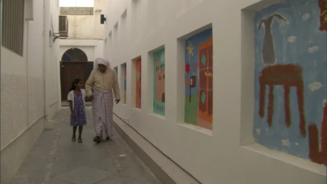 trackright of a grandfather in traditional bahraini costume and granddaughter walking in an alleyway in muharraq - senior men stock videos & royalty-free footage