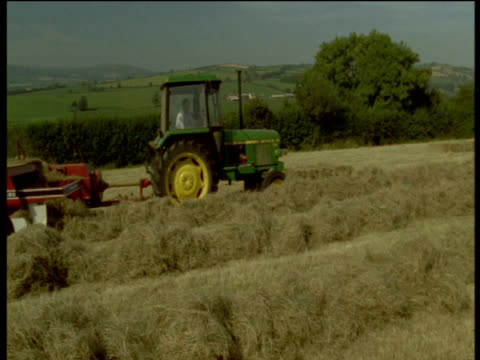 tractor and hay baler move left to right past camera, devon - devon stock videos & royalty-free footage