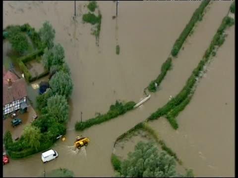 stockvideo's en b-roll-footage met tractor and van drive through flooded road during june 2007 floods sheffield - van
