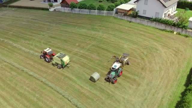 traktor sammelt einen heuballen auf dem feld - cereal plant stock-videos und b-roll-filmmaterial