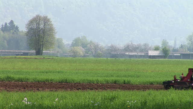 ms, tractor crossing field, slovenia - agricultural machinery stock videos & royalty-free footage