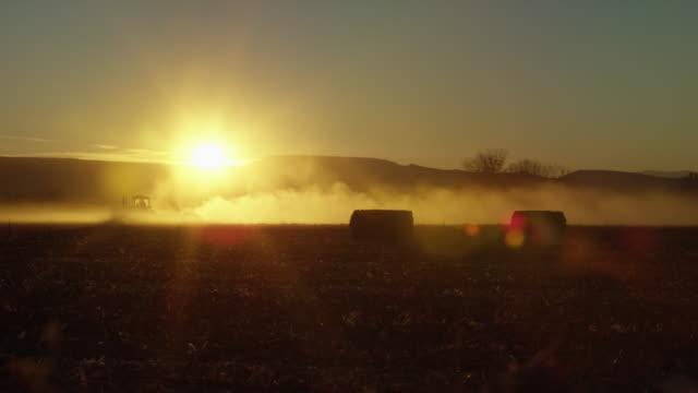 a tractor drives through a dusty, hazy corn field with hay bales in it at sunset with mountains in the background in western, colorado - hay stock videos and b-roll footage