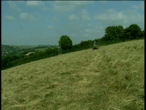 tractor drives towards camera whilst haymaking, devon - devon stock videos & royalty-free footage