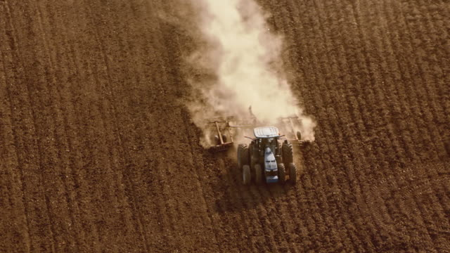 aerial tractor driving across a vast field in sunshine - agricultural machinery stock videos & royalty-free footage