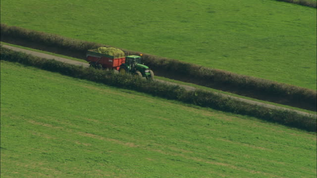 vidéos et rushes de aerial ws zi zo tractor driving down country road surrounded by green fields / burgundy, france - route de campagne