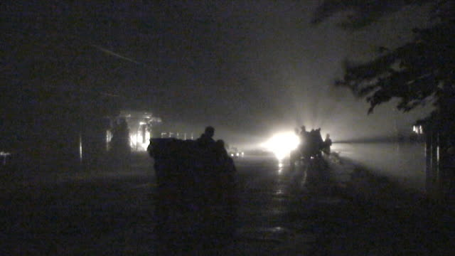 Tractor driving in furious winds illuminated by car headlights, Philippines, Typhoon Parma, 2009