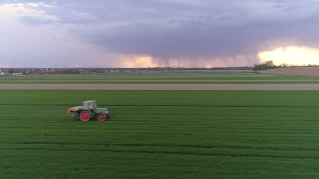 WS trekker rijden in weelderige, groene veld met storm wolken in de achtergrond