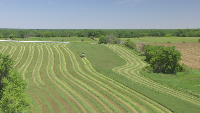 WS AERIAL POV Tractor harvesting grass in farmland / Monroe County, Iowa, United States