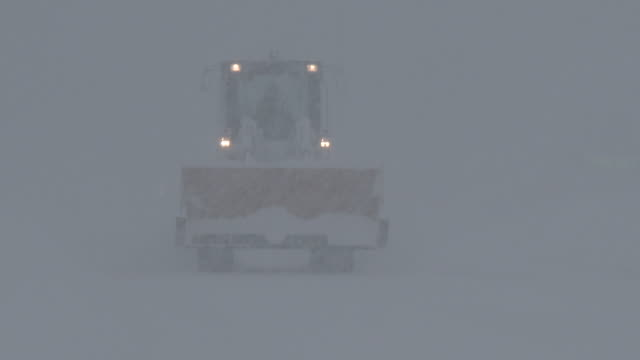 a tractor is barely visible in adams new york as the operator drives in near zero visibility during a lake effect snowstorm - scott mcpartland stock videos and b-roll footage