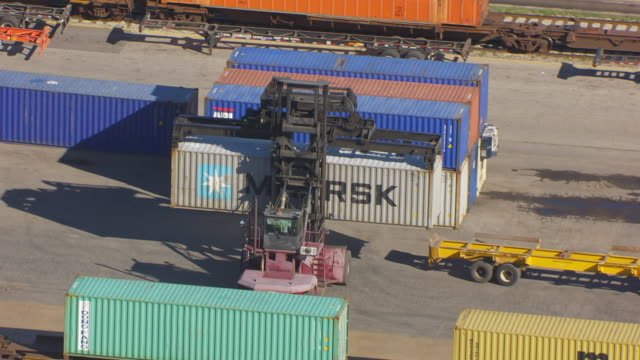 ws aerial pov tractor lifting cargo container on back of truck at belt railroad clearing yard / chicago, cook county, illinois, united states  - 操車場点の映像素材/bロール