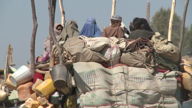 a tractor loaded with goods drives through a market. - provinz helmand stock-videos und b-roll-filmmaterial