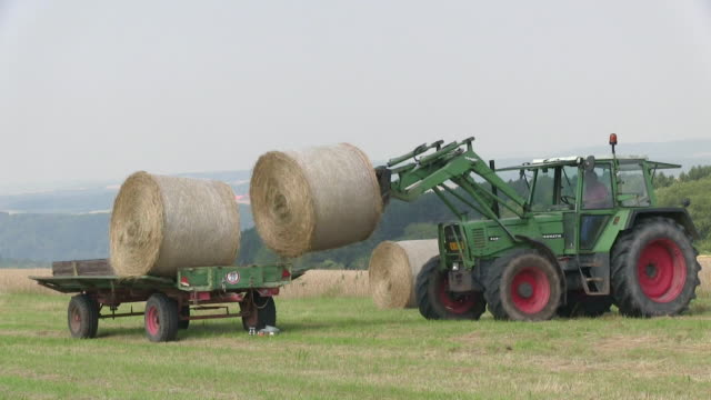 ms tractor loading bales of straw on field / saarburg, rhineland palatinate, germany - bale stock videos & royalty-free footage