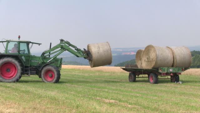ms pan tractor loading bales of straw on field / saarburg, rhineland palatinate, germany - bale stock videos & royalty-free footage