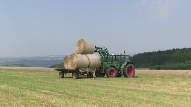 MS Tractor loading of bales of straw on field / Saarburg, Rhineland Palatinate, Germany