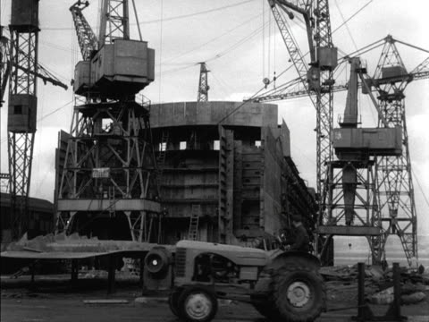 a tractor moves past a ship under construction at the port glasgow shipyard - costruttore navale video stock e b–roll