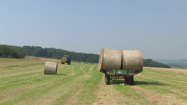 MS Tractor moving with picking bales of straw on field / Saarburg, Rhineland Palatinate, Germany