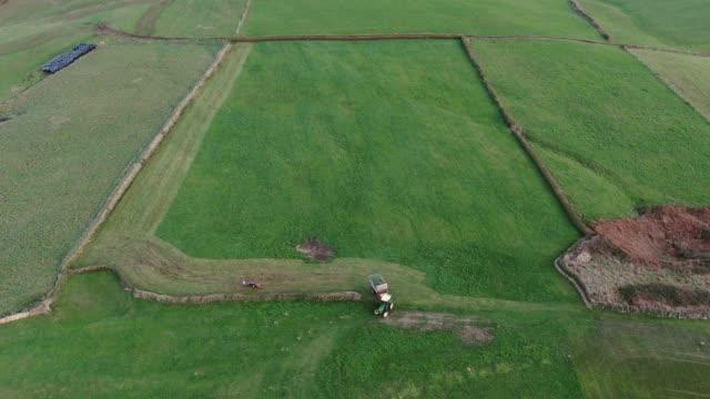 vidéos et rushes de tracteur tondant un grand champ vu d'en haut - tracteur