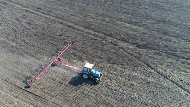 Tractor planting crops on a farm field, aerial view
