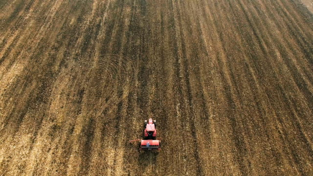 stockvideo's en b-roll-footage met trekker aanplant gewassen op een boerderij veld - volgen activiteit