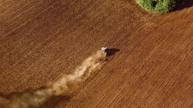 vídeos de stock e filmes b-roll de aerial tractor ploughing a vast field in sunshine - trator