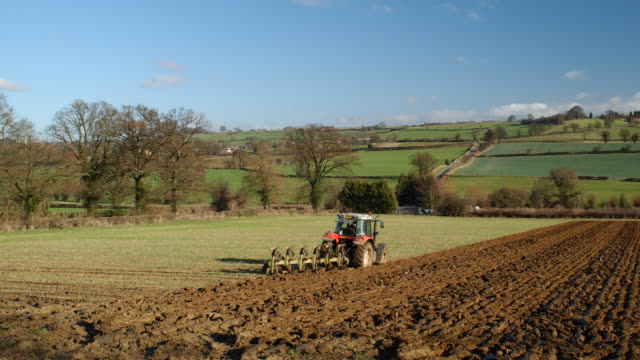 T/L tractor ploughing field in winter, takes 2, UK