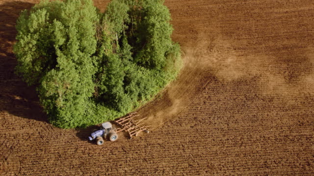 aerial tractor ploughing the field on a sunny day - plough stock videos & royalty-free footage
