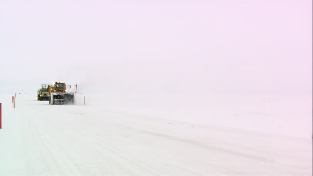TS Tractor plow, snow blower, and tanker truck driving across packed snow / Alaska, United States