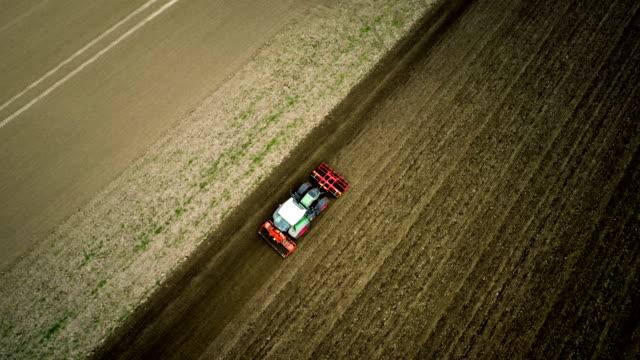 antenne: traktor pflügen ein feld - landwirtschaft - pflügen stock-videos und b-roll-filmmaterial