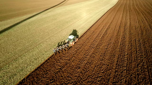 AERIAL: Tractor plowing a field