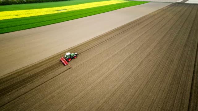 antenne: traktor ein feld pflügen - pflügen stock-videos und b-roll-filmmaterial