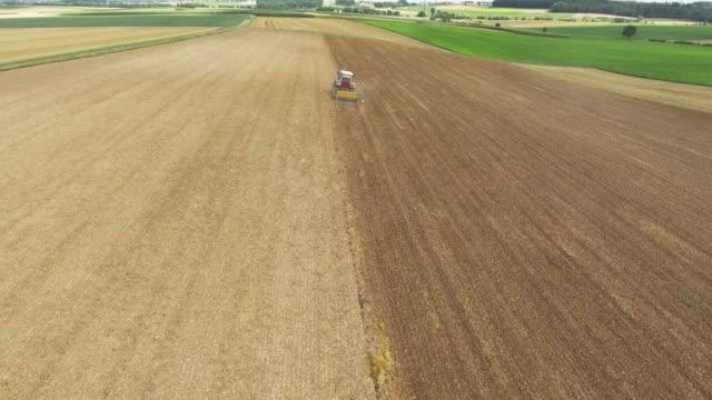 traktor pflügen einer getreide-feld-überführung - pflügen stock-videos und b-roll-filmmaterial