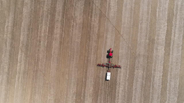 tractor plowing and fertilizing the agricultural fields in the springtime nearby lyndon township, illinois, usa. aerial drone video with the panning camera motion following the tractor. - illinois stock videos & royalty-free footage